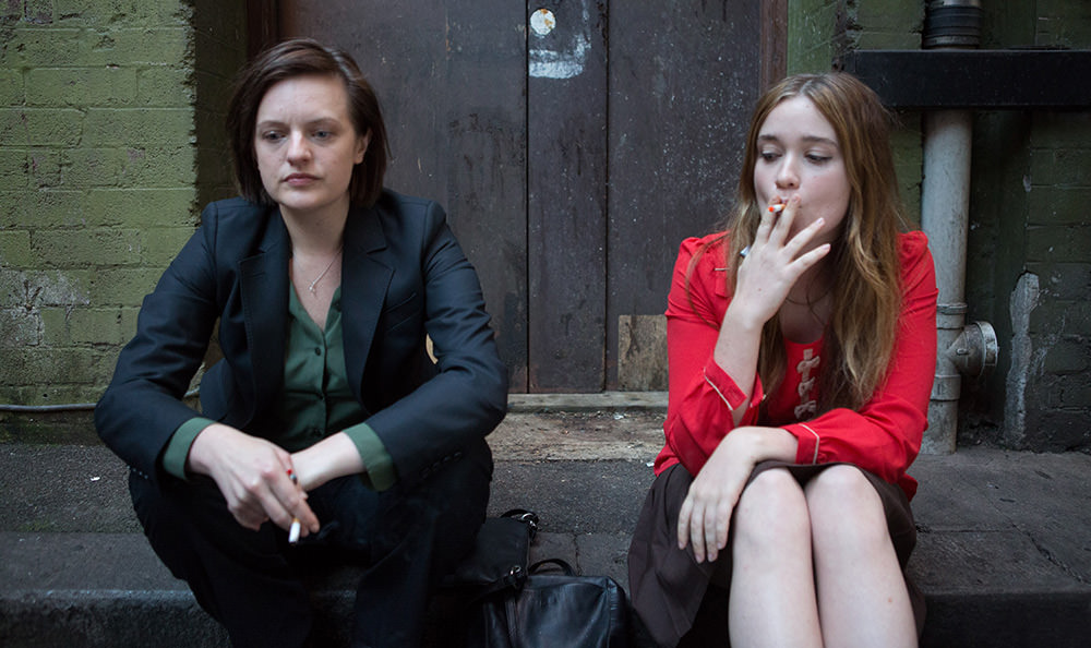 Two women sitting on a stoop smoking
